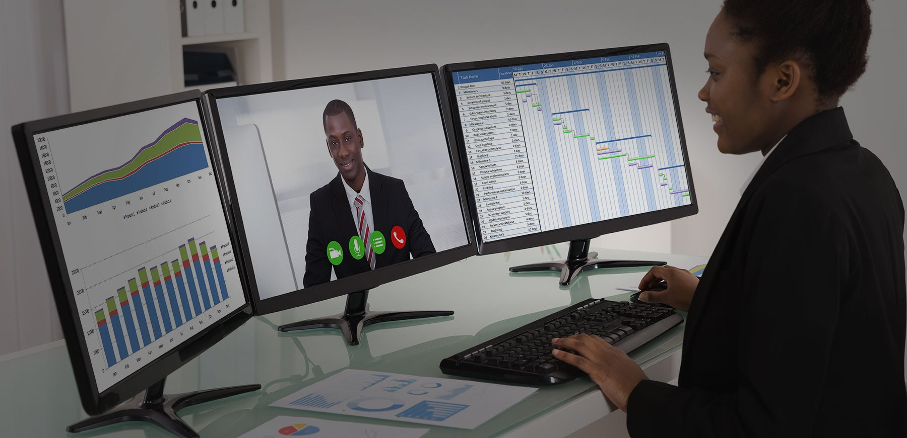 Une dame en appel video avec trois ecrans d'ordinateur